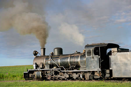 Vintage steam locomotive with billowing smoke and steam photo