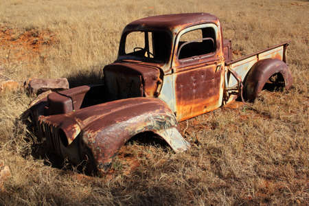 Wreck of a rusty old pickup truck out in the field  Stock Photo