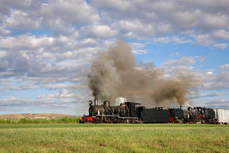 Vintage steam locomotive with billowing smoke and steam