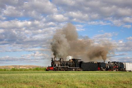 locomotora: Locomotora de vapor de época con nubes de humo y vapor Editorial