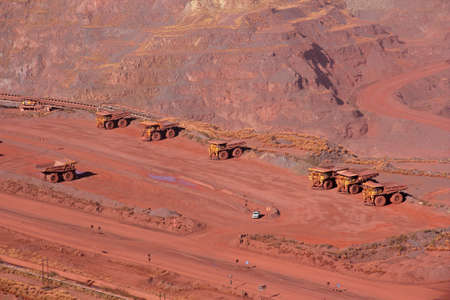 Large, open-pit iron ore mine with trucks photo