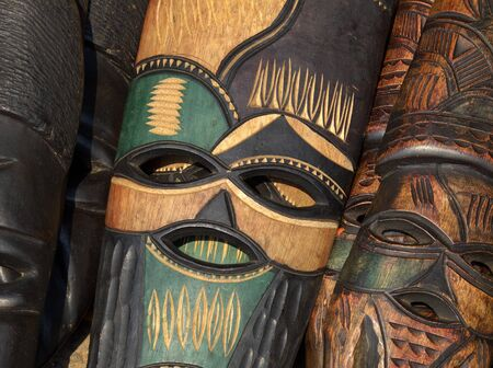 Decorated hand made wooden mask carved from the wood of an African tree Stock Photo - 12030011