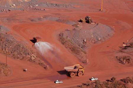 cast: Large, open-pit iron ore mine with trucks
