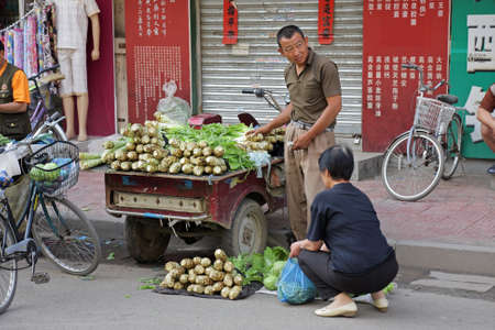 HoHot, Inner Mongolia, northern China, June 29, 2008 - A Chinese man selling his fresh produce on a street - an example of the informal economic market of China Stock Photo - 12689926