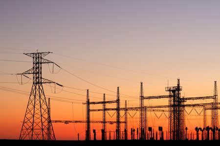 torres de alta tension: Siluetas de torres de energía contra un cielo rojo al atardecer
