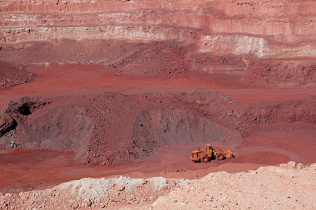 Large, open-pit iron ore mine showing the various layers of soil and iron rich ore photo
