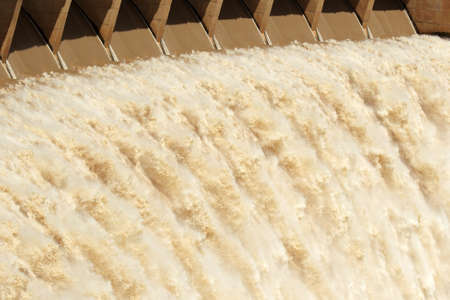 sluice: Strong flowing water released from the open sluice gates of a large dam