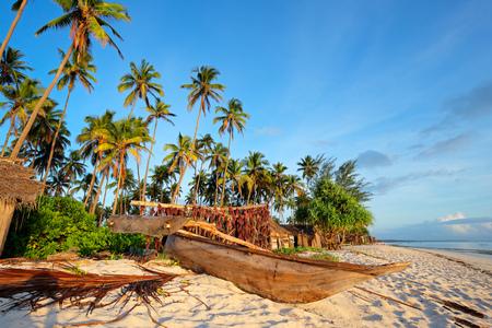 木製ヨット - ダウ船 - とザンジバルの熱帯ビーチ島でヤシの木 写真素材