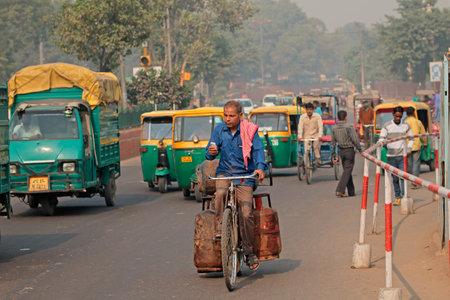 デリー, インド - 2015 年 11 月 20 日: カラフルなトゥクトゥク自動車と大気汚染の目に見えるスモッグで混雑している交通自転車男