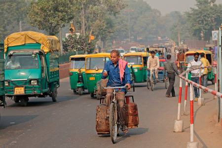 Delhi, India - November 20, 2015: Man on a bicycle in the crowded traffic with colorful Tuk-Tuk vehicles and visible smog of air pollution Editoriali
