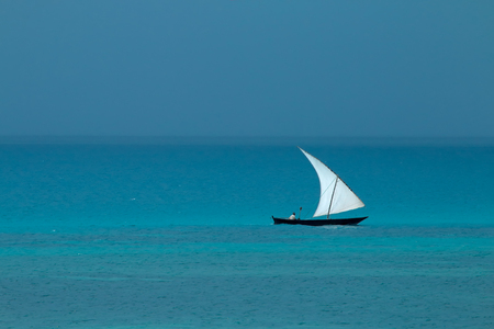 Wooden sailboat (dhow) on water with cloudy sky, Zanzibar island