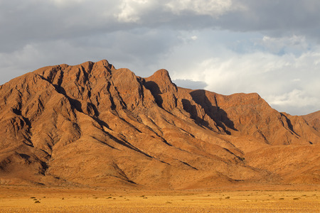 Rugged mountain landscape with cloudy sky, Namib desert, Namibia Imagens