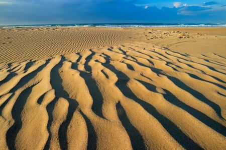 Scenic beach early morning with wind-blown patterns in the sand, South Africa Stock Photo