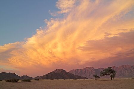 Namib desert landscape at sunset with rugged mountains and dramatic clouds, Namibia Stock Photo