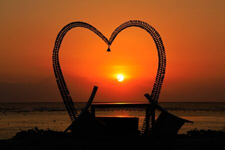 Romantic heart shaped silhouette with chairs on a scenic tropical beach at sunset