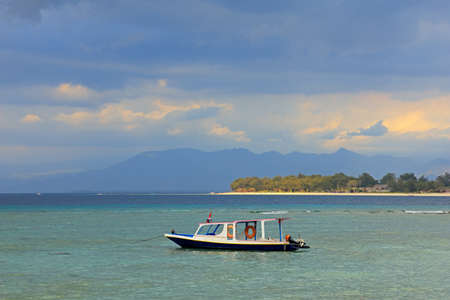 Scenic tropical Indonesian island with anchored boat against a dark sky with clouds
