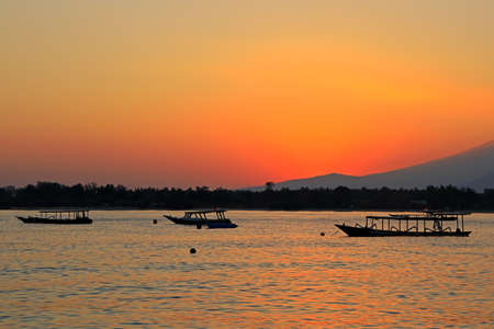Scenic beach with boats silhouetted at sunset on a tropical island of Indonesia Stock Photo