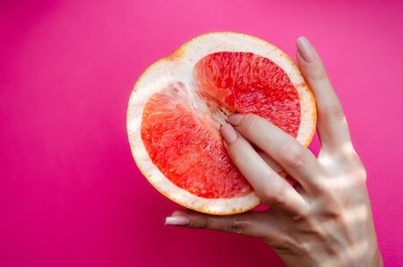 Vagina symbol. Two fingers on grapefruit on pink background. Sex concept. Zdjęcie Seryjne