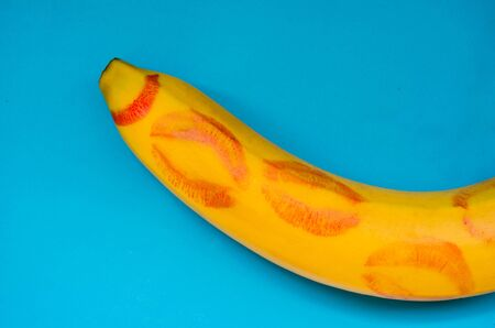 red lipstick on a banana on a blue background. concept oral sex Stock Photo
