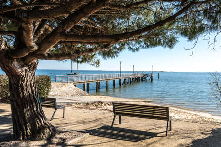 Cap Ferret, Arcachon Bay, France. Public bench and jetty Stock Photo - 119381571