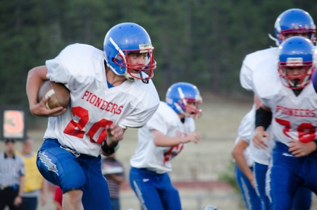 linemen: Close up of High School varsity football player running withfootball in red, white, and blue uniform