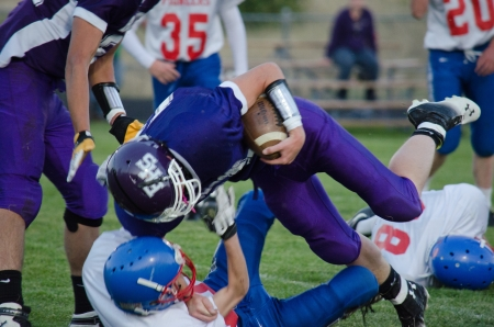 Close up of High School varsity football player being tackled with football in purple uniform