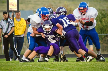Offensive high school varsity football player in pruple uniform being tackled by several defensemen in red, white and blue uniform