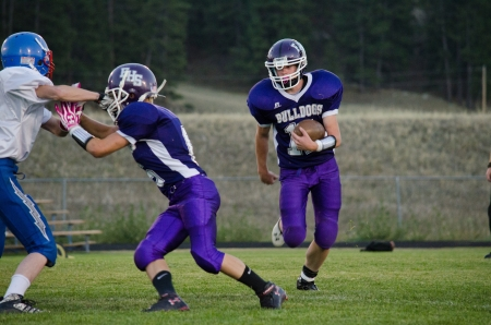 High school varsity quarterback in purple uniform avoiding tackle