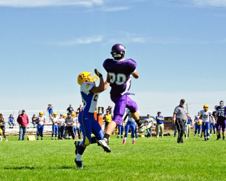 High School varsity football player in purple uniform leaping high into the air to catch football