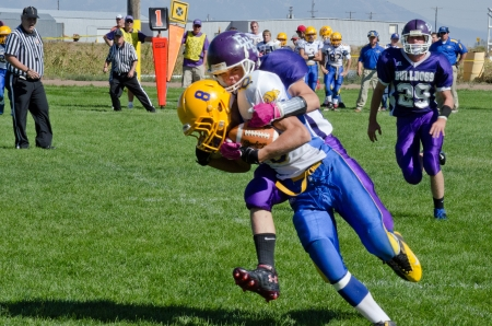High school varsity football player in blue and yellow uniform being tackled near the  sidelines by player in purple uniform