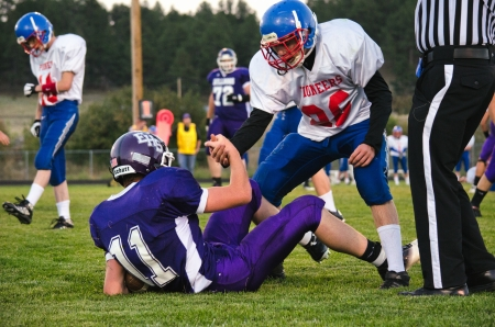 high school varsity football players showing sportsmanship helping each other up from the ground after a play Editoriali