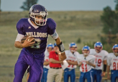 Isolated high school varsity player in purple uniform running with football