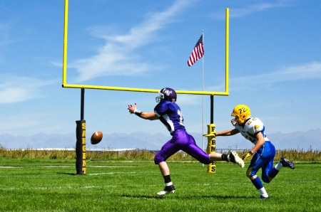 high school varsity football player stretching to catch football near endzone