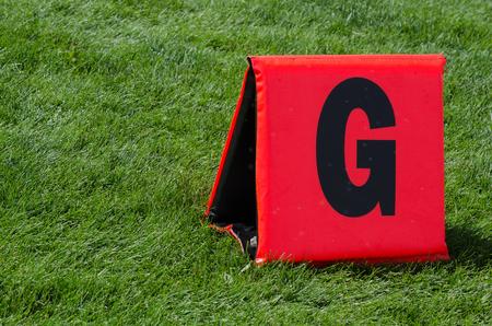 reddish orange tnet style goal line marker on green grass