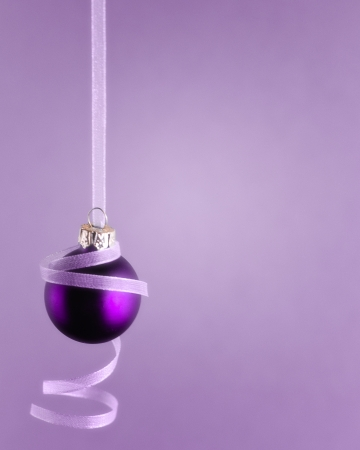 monotone: Monotone image of purple ornament hanging from light purple curly ribbon  Isolated purple vignette background