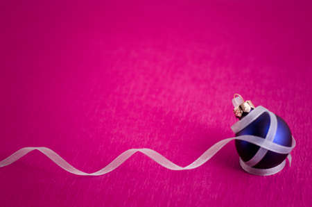Image of blue ornament with white curly ribbon  Isolated on pink background  photo