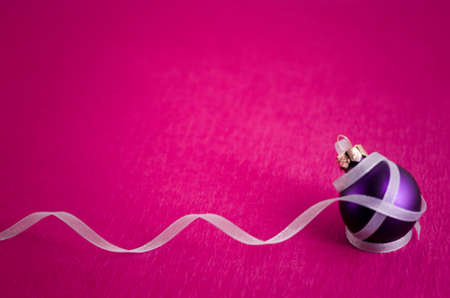 Image of purple ornament with white curly ribbon  Isolated on pink background  photo