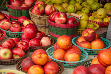 Colorful baskets full of fresh apples and peaches