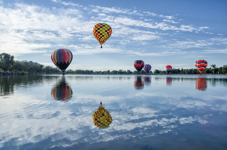 Several colorful hot air balloons rising above a clear lake with a clear reflection of all balloons on the lake Redakční