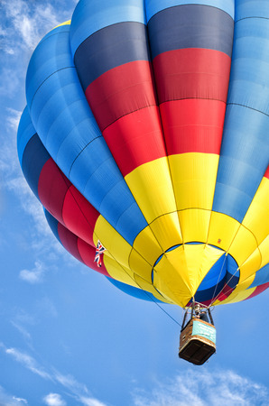One colorful, red, blue, and yellow hot air balloon rising against a bright blue sky with whispy white clouds