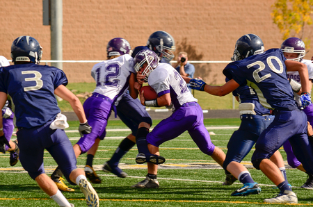 school sports: Football player pushing through several other opponents