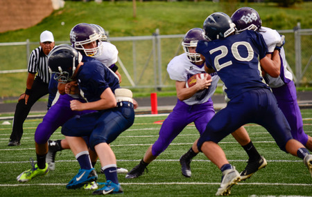 linemen: Football player gripping ball while breaking through defensive linemen Editorial