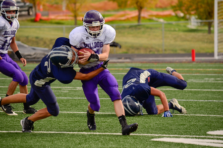 Football player gripping ball while being tackled