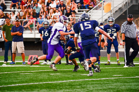 sporting event: Football player with ball running into opposing team