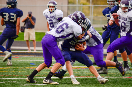 school sports: Football player being tackled