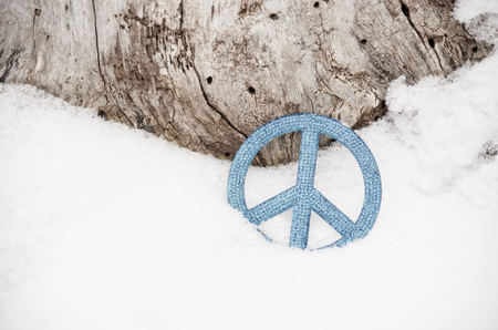 trees seasonal: Light Blue peace sign in snow against tree