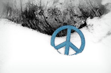 blue peace sign ornament in the snow leaning against a tree