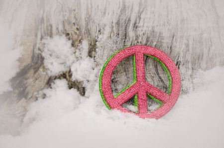 red and green peace sign in snow with white vignette