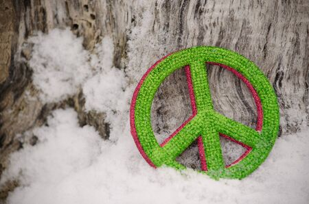 Green and red peace sign ornaments leaning against a tree in the snow Archivio Fotografico