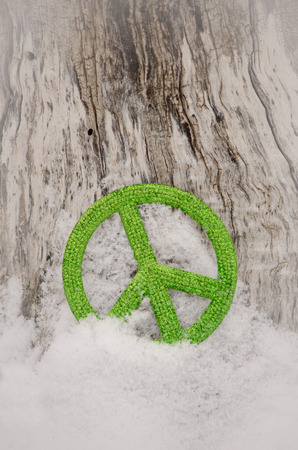 green peace sign in snow against tree with vignette Archivio Fotografico